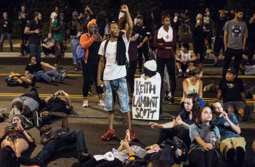 """Black man with fist raised surrounded by people on ground and white sign reading """"Keith Lamont Scott"""" in black ink"""