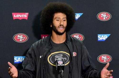 Colin Kaepernick in black jacket and black t-shirt with red and gold logos on each