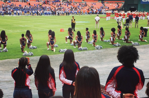 Black women in black cheerleading attire kneeling on green and white  football field sideline 9030cc2c0