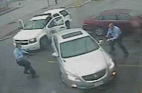 grainy video of policemen in blue uniforms near silver car and white police SUV