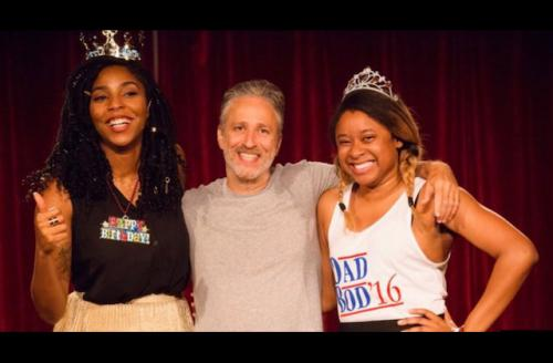 two black women flank a white man while wearing silver tiaras and multi-colored necklaces