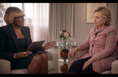Mary J. Blige in black blazer and dress, Hillary Clinton in pink jacket, both seated on cream-colored armchairs