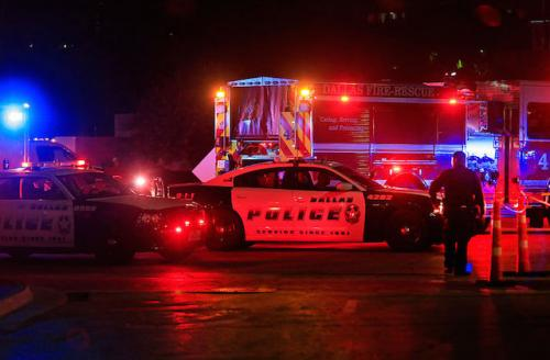 Dallas Police Department cars with lights on on dark street