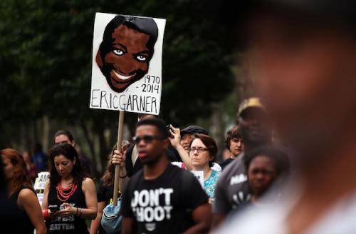 Drawing of Eric Garner on white poster with black text, held by man in black t-shirt with white lettering