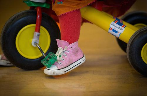 Child's legs on a tricycle.