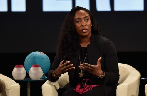 Black woman in black shirt, pants and jacket on tan brown chair