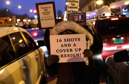 """Person wearing massive furry hood holds sign that reads: """"16 shots and a cover up = resign!"""""""