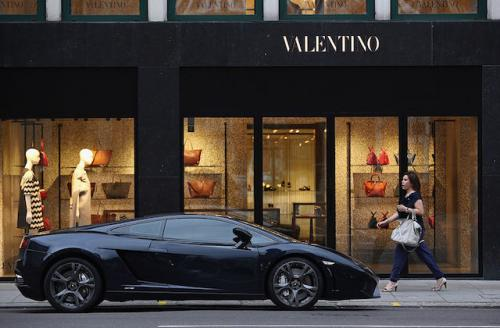 Valentino store front, fancy black car parked out front, woman walking by