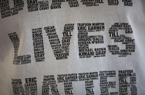 Closeup of white t-shirt with names of Black people killed by police and vigilantes printed in black