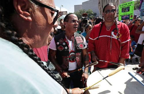Members of a drum group sing during a rally on Dakota Access Pipeline August 24, 2016, outside U.S. District Court in Washington, DC.