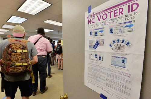 A poster outlines North Carolina voter identification requirements, people stand in line at the polls