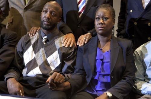 Tracy Martin gray and white argyle sweater next to Sybrina Fulton in black cardigan and blue shirt, holding hands