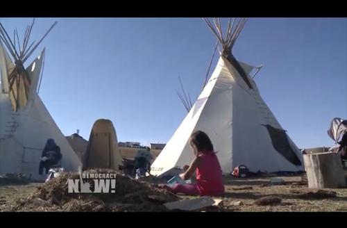 A child plays near teepees on a #NoDAPL camp near the Cannonball River.