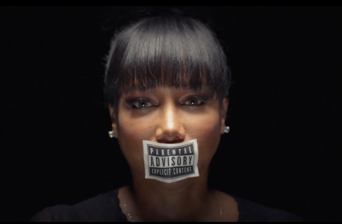 """Michele with black-and-white """"parental advisory"""" sticker on mouth against black background"""