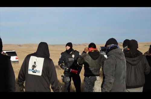 """Police officers threaten water protectors with pepper spray near a Dakota Access Pipeline work site. """"You are all under arrest,"""" he shouted."""