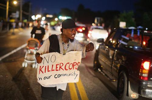 "Protester holding sign that says, ""No killer cops in our community"""