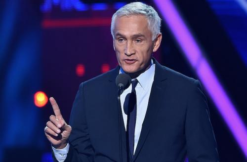 Man with white hair in navy suit and light blue shirt with black microphone against purple background
