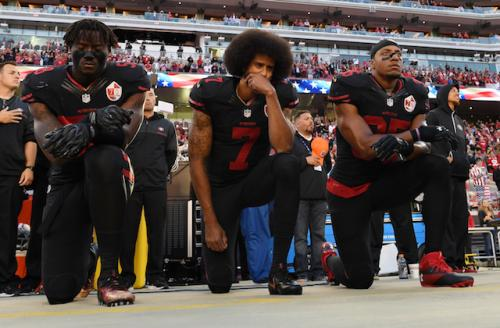 Three Black men kneeling in black jerseys with red lettering against green background