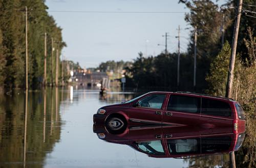 A vehicle is partially submerged by floodwaters from the Lumber River on October 12, 2016, in Lumberton, North Carolina.