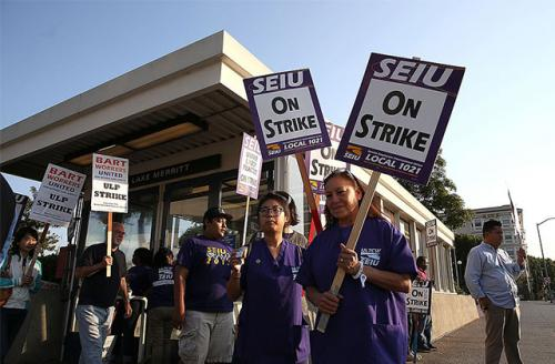 Bay Area Rapid Transit (BART) union workers with SEIU Local 1021 hold signs as they picket in front of the Lake Merritt station on July 2, 2013, in Oakland, California.