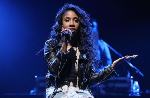Black woman in black leather jacket sits on stage holding a microphone