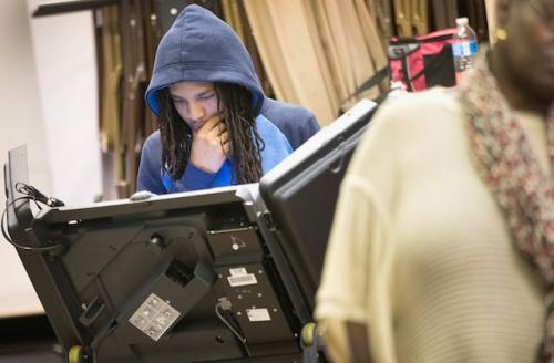 Young Black man with dredlocks and a blue hoodie votes in Ferguson