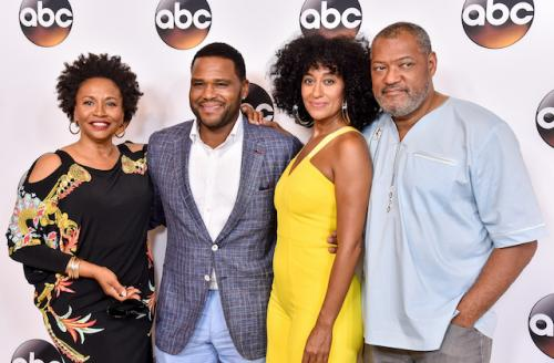 """Four Black people stand with arms around shoulders against white wall with black """"ABC"""" logos"""