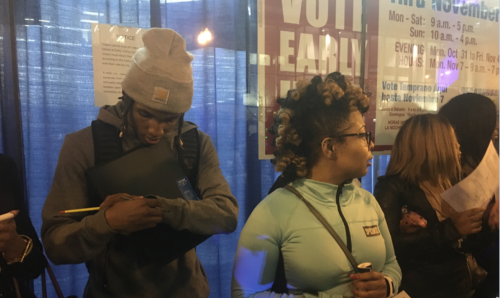 A young man wearing a gray wool cap and a young woman with spiral blonde curls wait to vote on November 7, 2016
