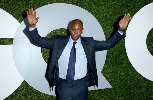 Black man with hands up in air wearing light blue shirt and dark blue tie under navy suit against grey and green background