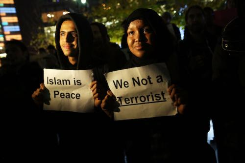 "A young Muslim man wearing a black hoodie and a young woman wearing a hijab hold up signs that say ""Islam is peace"" and ""We not a terrorist"""