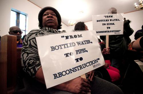 A woman holds a sign while attending a prayer service before participating in a national mile-long march to highlight the push for clean water in Flint February 19, 2016, in Flint, Michigan.