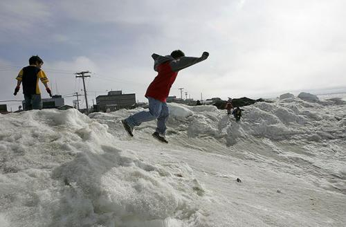 Inupiat eskimo children play along the banks of the frozen Arctic Ocean June 7, 2006, in Browerville, Alaska. Scientists now know that climate change will submerge or destroy much of their coastal land, including the village of Shaktoolik.