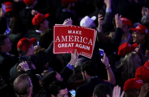 Red sign with white text held by White hand in crowd