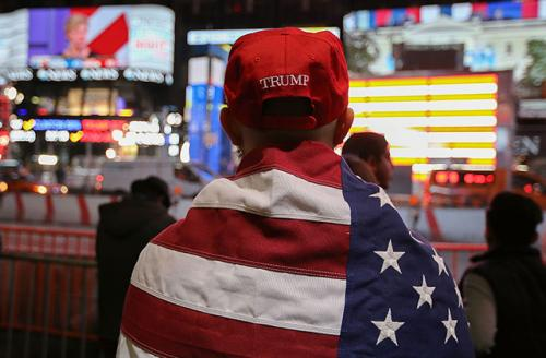 A Donald Trump supporter watches the screens outside Times Square Studios as he awaits the results of the U.S. presidential election on November 9, 2016, in New York City.