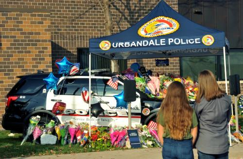 Black and white police SUV covered in flowers and other commemorations against red brick background and under navy tent with white lettering