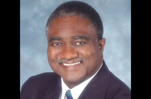 George Curry in navy suit and multicolored tie with white shirt, against light blue background