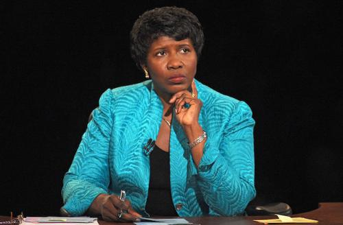 Gwen Ifill in teal blazer, sitting at a desk