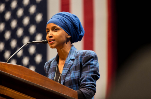 Black woman in hijab speaks at a podium with American flag behind her