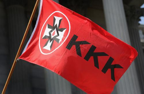 "Red flag with black letters reading ""KKK"" and black, red and white cross"