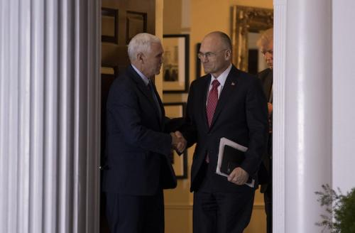 White man in navy suit shakes hand of White man in black suit with red tie with White man in navy suit in background against white pillars
