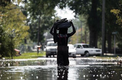 A man carries personal items through a flooded street caused by remnants of Hurricane Matthew on October 11, 2016, in Fair Bluff, North Carolina. Storms like these will become more frequent, according to a new study.