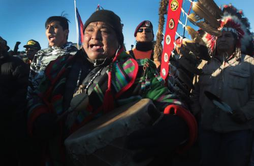 Native person holds brown drum and wears black hat and multicolored top in front of other native peoples in multicolored clothing and attire against blue sky