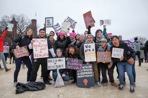 A group of people with signs stand on the national mall