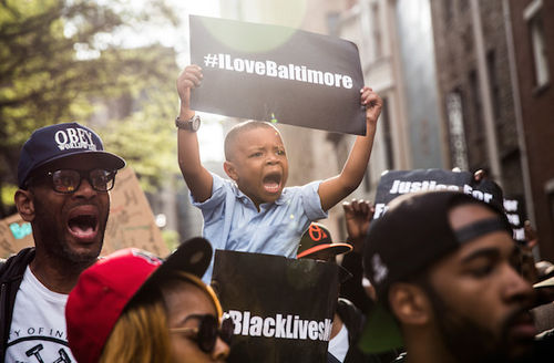 "Black child holds black sign with white text reading ""#ILoveBaltimore"" while sitting on shoulders next to Black adults holding black signs with white text reading ""#BlackLivesMatter"" and ""Justice for Freddie Gray"" amidst yellow sun glare"