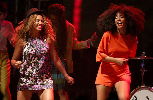 Two Black women smile and dance on stage