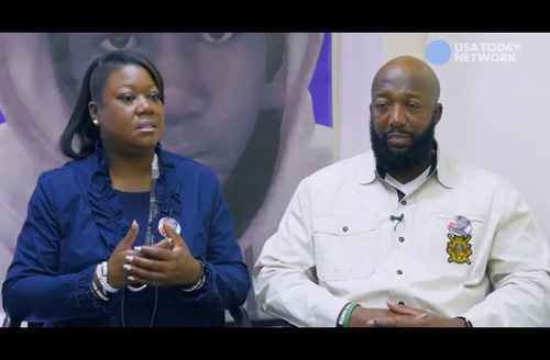 Black woman in blue blouse and shirt next to Black man in white shirt in front of background with purple and white rendering of Black child