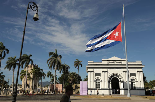 Flag with blue and white stripes, red triangle and white star flies at half staff with blue sky, green and brown palm trees and brown-gray building in the background