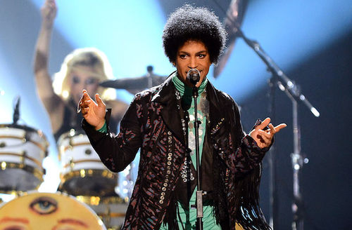 Black man in green outfit under purple patterned jacket behind black microphone stand and against blue lit background with White woman behind yellow drumset