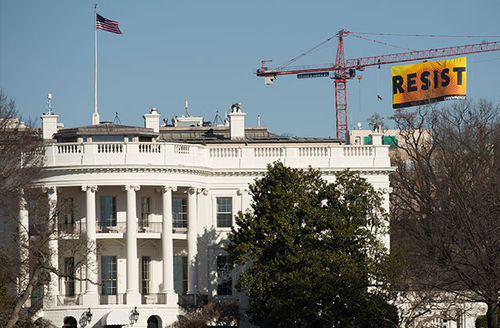 """Greenpeace activists deploy a banner on a construction crane near the White House reading """"RESIST"""" on President Donald Trump's fifth day in office, January 25, 2017."""