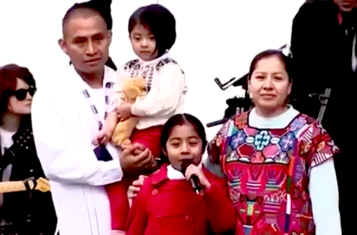 A 6-year-old Latinx girl wearing a red dress stands in front of her parents and baby sister making a speech about fair immigration at the Women's March on Washington